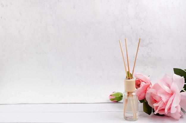 Deodorante per ambienti bastoni su fondo di legno bianco con rose rosa, copia dello spazio