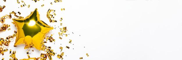 Aerostati dorati a forma di stella e coriandoli su sfondo bianco.