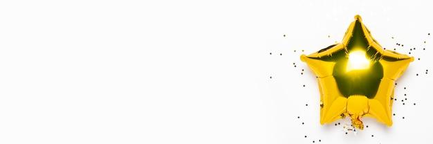 Air palloncini dorati a forma di stella e caramelle su uno sfondo bianco.