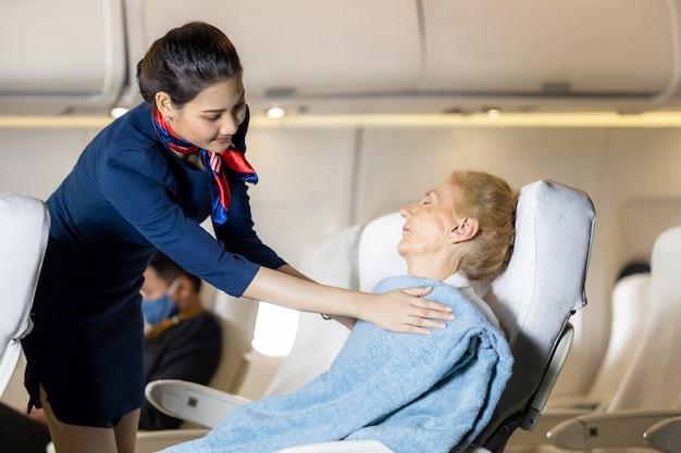 Servizio di hostess o hostess che copre una coperta per i passeggeri in aereo, assistente di volo asiatico o hostess che copre una coperta per passeggeri caucasici per dormire sull'aereo