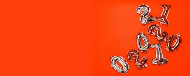 Numero di palloncini ad elio di uno e zero su sfondo rosso