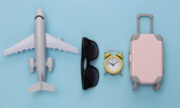 Aereo, mini bagaglio da viaggio, occhiali da sole e sveglia su sfondo blu.