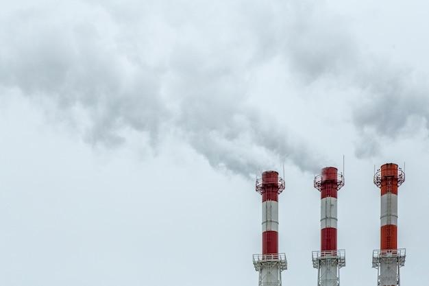 Concetto di inquinamento dell'aria. fumo della fabbrica dai tubi su una priorità bassa del cielo grigio