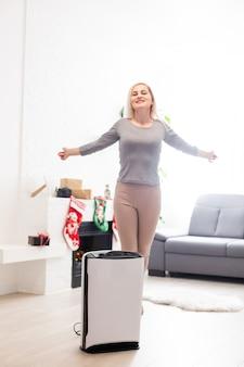 Purificatore d'aria in un soggiorno, donna che lavora con un laptop con filtro per camera bianca