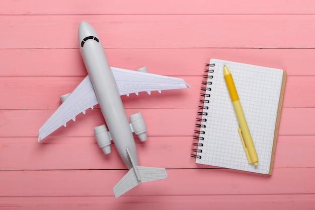 Turismo aereo o pianificazione del viaggio, laici piatta. statuetta di aeroplano su un legno rosa