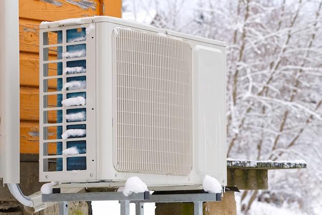 Pompa di calore aria-acqua nei pressi di una vecchia casa in legno in inverno.
