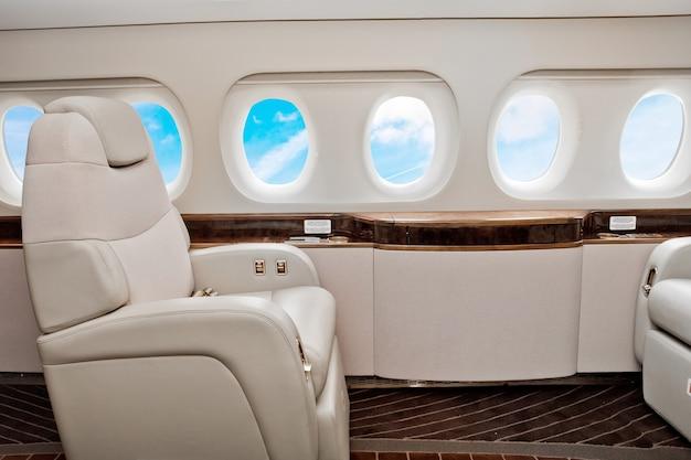 Interni di classe business di aeromobili con cielo blu fuori dagli oblò