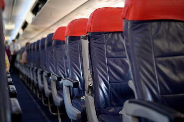 Una cabina di un aereo con file di sedili passeggeri vuote.