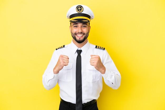 Uomo pilota arabo aereo isolato su sfondo giallo che celebra una vittoria nella posizione del vincitore