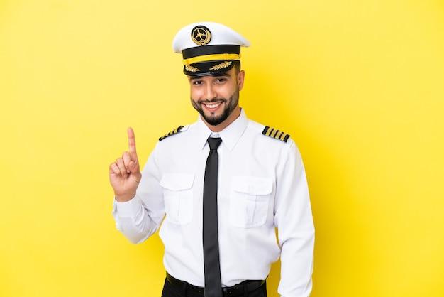 Uomo pilota arabo aereo isolato su sfondo giallo che mostra e solleva un dito in segno del meglio
