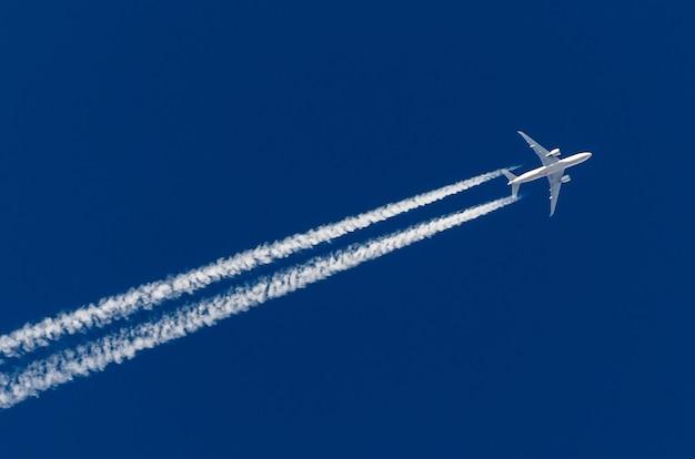 Nuvole di scia di condensazione dell'aeroporto di aviazione dei grandi quattro motori dell'aeroplano.