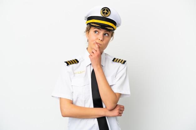 Pilota della donna bionda dell'aeroplano isolato su fondo bianco che ha dubbi mentre guarda in su