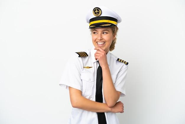 Pilota della donna bionda dell'aeroplano isolato su fondo bianco che guarda al lato e che sorride