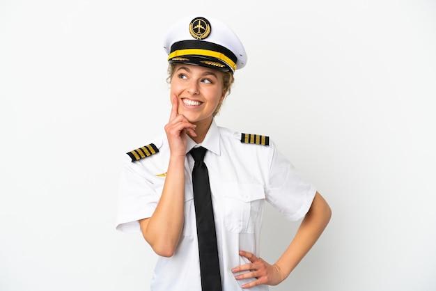 Pilota della donna bionda dell'aeroplano isolato su fondo bianco che pensa un'idea mentre guarda in su