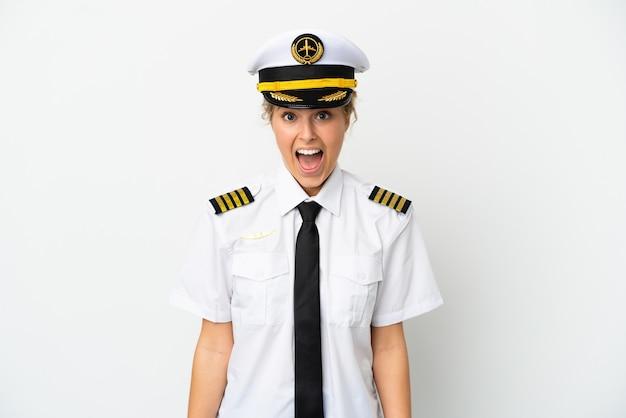 Pilota di donna bionda aereo isolato su sfondo bianco con espressione facciale a sorpresa