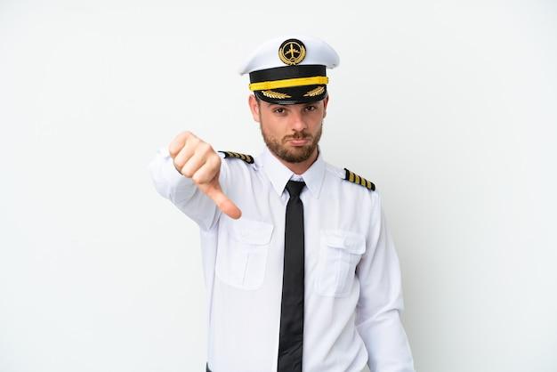 Pilota brasiliano dell'aeroplano isolato su fondo bianco che mostra pollice giù con espressione negativa with