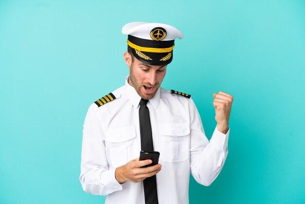 Pilota caucasico dell'aeroplano isolato su sfondo blu sorpreso e inviando un messaggio