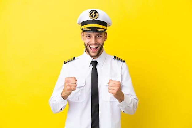 Pilota caucasico dell'aeroplano isolato su sfondo giallo che celebra una vittoria nella posizione del vincitore