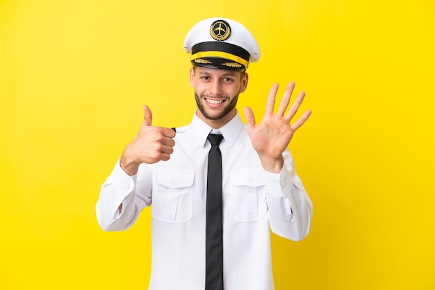 Pilota caucasico dell'aeroplano isolato su sfondo giallo contando sei con le dita