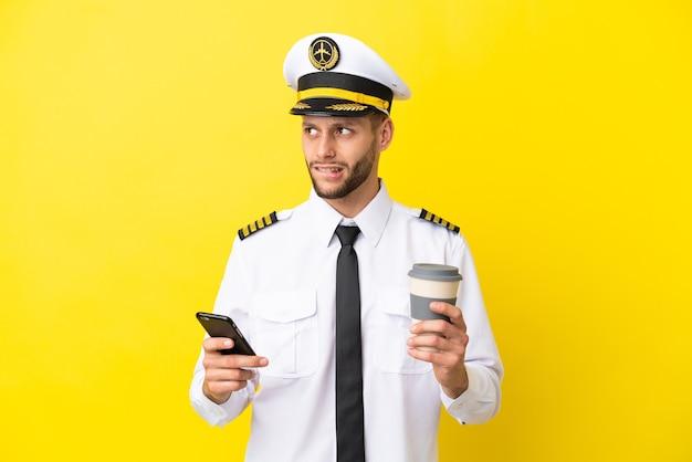 Pilota caucasico dell'aeroplano isolato su sfondo giallo che tiene il caffè da portare via e un cellulare mentre pensa a qualcosa