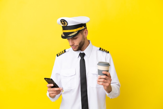 Pilota caucasico dell'aeroplano isolato su sfondo giallo che tiene il caffè da portare via e un cellulare