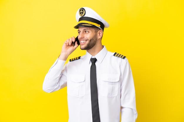 Pilota caucasico dell'aeroplano isolato su sfondo giallo che tiene una conversazione con il telefono cellulare