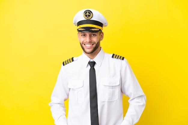 Pilota caucasico dell'aeroplano isolato su sfondo giallo ridendo