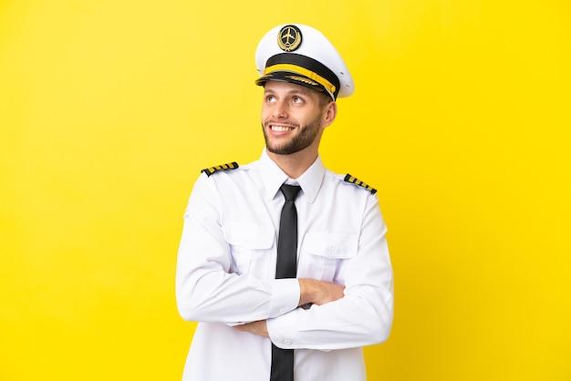 Pilota caucasico dell'aeroplano isolato su sfondo giallo alzando lo sguardo mentre sorride