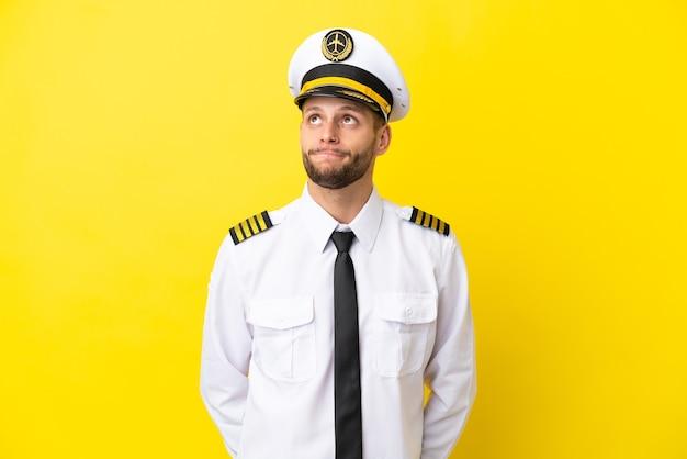 Pilota caucasico dell'aeroplano isolato su sfondo giallo e alzando lo sguardo