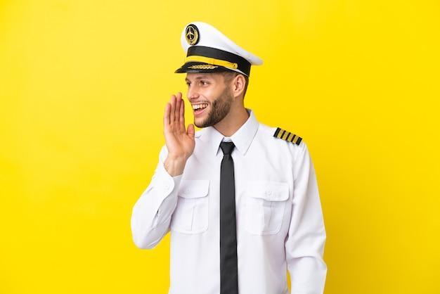Pilota caucasico dell'aeroplano isolato su sfondo giallo che grida con la bocca spalancata al laterale