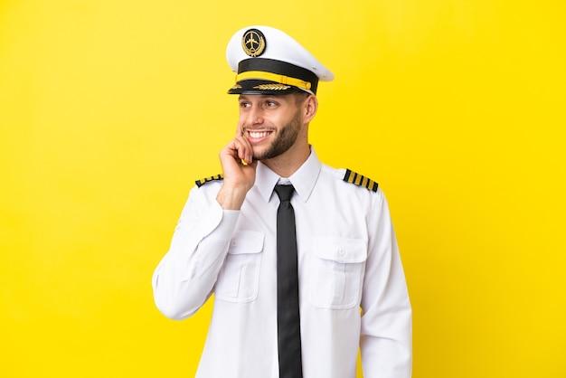 Pilota caucasico dell'aeroplano isolato su sfondo giallo pensando a un'idea mentre guarda in alto