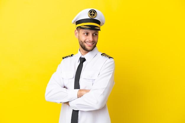 Pilota caucasico aereo isolato su sfondo giallo con le braccia incrociate e felice
