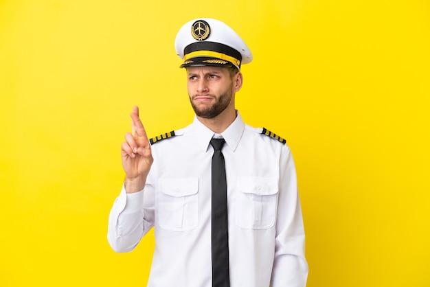 Pilota caucasico dell'aeroplano isolato su sfondo giallo con le dita incrociate e augurando il meglio