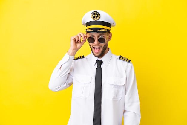 Pilota caucasico dell'aeroplano isolato su sfondo giallo con gli occhiali e sorpreso