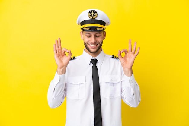 Pilota caucasico dell'aeroplano isolato su sfondo giallo in posa zen
