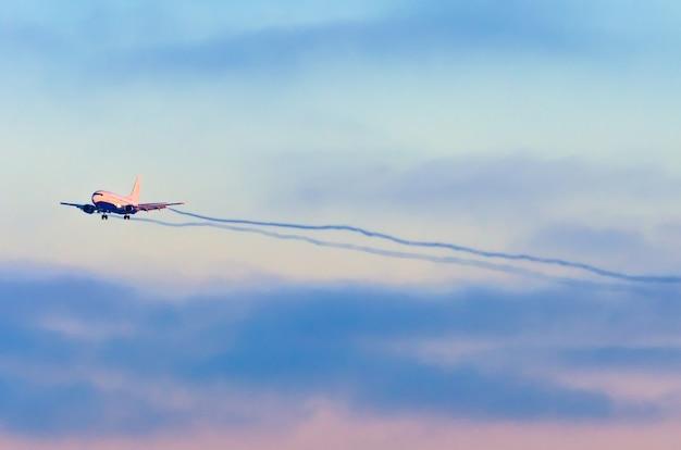 L'aereo si avvicina all'aeroporto prima di atterrare tra le nuvole al tramonto.