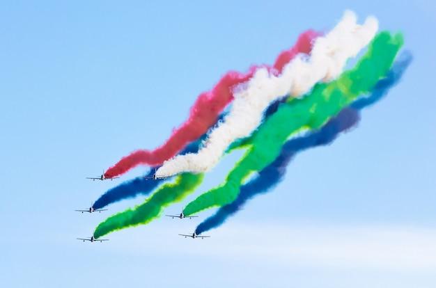I caccia dell'aeroplano fumano lo sfondo delle nuvole del cielo.