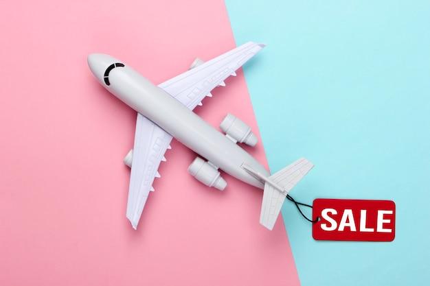 Statuetta di aeroplano con etichetta di vendita rossa su pastello blu rosa.