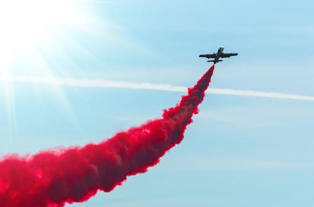Mosca dell'aeroplano in zigzag con un fumo rosso della traccia nel cielo.