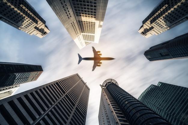 Aeroplano che sorvola edifici commerciali della città, grattacieli