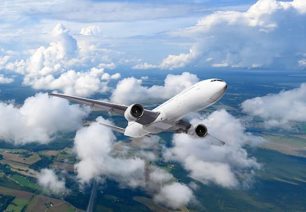 Aeroplano che vola sopra le nuvole sullo sfondo del cielo blu