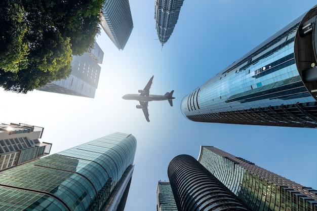 Aeroplano che vola in basso sopra gli edifici per uffici del highrise