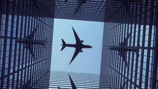 Aeroplano che vola sopra i moderni grattacieli contro un bel cielo blu