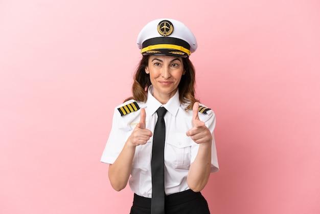 Donna pilota di mezza età dell'aeroplano isolata su sfondo rosa rivolta verso la parte anteriore e sorridente