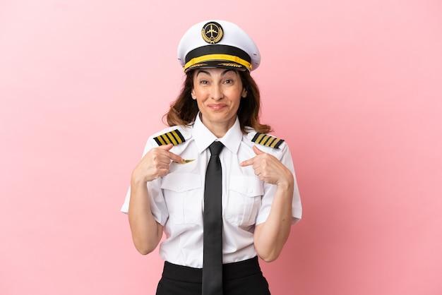 Donna pilota di mezza età dell'aeroplano isolata su sfondo rosa con espressione facciale a sorpresa