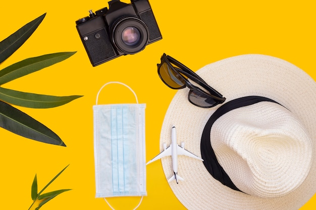 Modello di aeroplano, laptop, telefono, mascherina medica, macchina fotografica e occhiali. annullamento del volo a causa dell'impatto del concetto di turismo del coronavirus covid-19. copia spazio sfondo giallo