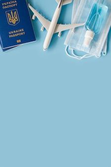 Modello di aeroplano, passaporti, maschere per il viso e disinfettante.