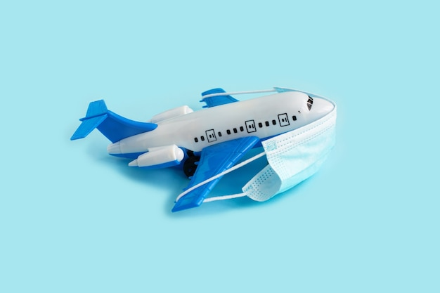 Modello di aeroplano con mascherina medica protettiva su un blu