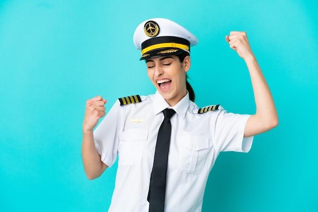 Donna caucasica pilota di aeroplano isolata su fondo blu che celebra una vittoria