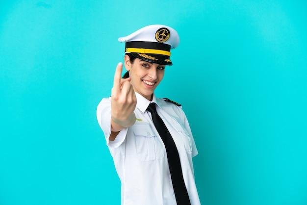 Pilota di aeroplano donna caucasica isolata su sfondo blu facendo gesto venuta